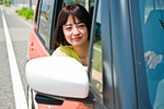 車の運転席から外を見る女性