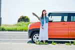 故障した車の前で電話する女性