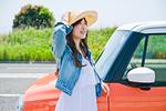 車の前で笑顔で立つ女性