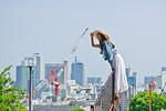 柵に登り街を見下ろす女性