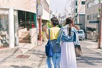街を歩く女性二人の後ろ姿