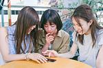スマホを見ながら会話する女性三人