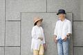 タイトル:壁の前に立つシニア夫婦
