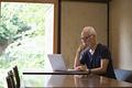 タイトル:ノートPCで作業するシニア男性