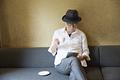 タイトル:コーヒーを飲みながらタブレットPCを見るシニア男性