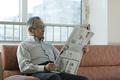 タイトル:新聞を読むシニアの男性