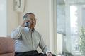 タイトル:スマートフォンで通話するシニアの男性