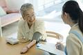 タイトル:血圧を測るシニアの女性