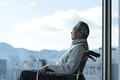 タイトル:車椅子に座るシニアの男性
