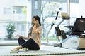 タイトル:スポーツジムで休憩するシニアの女性