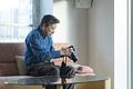 タイトル:カメラをいじるシニアの男性