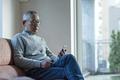 タイトル:音楽に聞き入るシニアの男性