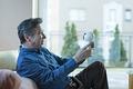 タイトル:コミュニケーションロボットと遊ぶシニアの男性