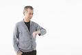 タイトル:腕時計を見るシニアの男性