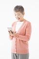 タイトル:スマートフォンを操作するシニアの女性