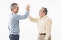 タイトル:ハイタッチをするシニアの男性2人