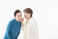 タイトル:ひそひそ話をするシニアの女性2人