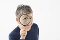 タイトル:ルーペを覗き込むシニアの女性