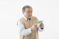 タイトル:通帳を見るシニアの男性
