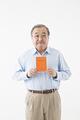 タイトル:年金手帳を持つシニアの男性