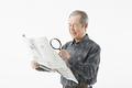 タイトル:ルーペで新聞を読むシニアの男性