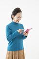 タイトル:電卓を持つシニアの女性