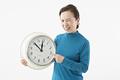 タイトル:時計を指して苦い顔をするシニアの女性