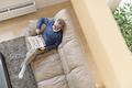 タイトル:ソファーでくつろぐ年配の男性