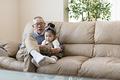 タイトル:ソファーで孫と遊ぶおじいちゃん