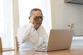タイトル:ノートパソコンを使うシニアの男性