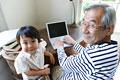 タイトル:パソコンをするシニアと孫