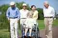 タイトル:シニアと車椅子を押す介護士