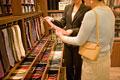 タイトル:ネクタイを選ぶ女性と店員