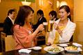 タイトル:居酒屋で乾杯をする女性