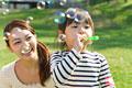 タイトル:シャボン玉を吹く女の子と母親