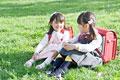 タイトル:芝生の上で話す新入学生