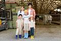タイトル:牛舎の前に立つ家族のポートレート