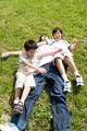タイトル:芝生に寝転がる親子