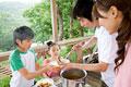 タイトル:ウッドテラスで食事の準備をする家族