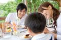 タイトル:ウッドテラスで食事をする家族