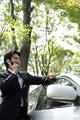タイトル:車の傍に立って携帯電話で会話する男性