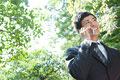 タイトル:木々の緑の下で携帯電話で会話している男性
