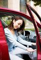 タイトル:車から降りる若い女性