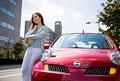 タイトル:車の前に立つ若い女性