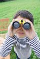 タイトル:双眼鏡で遠くを見る男の子