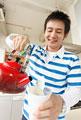 タイトル:カップ麺に湯を注ぐ男性