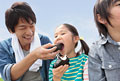 タイトル:土手でおにぎりを食べる父と子供2人