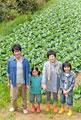 タイトル:畑の前に立つ親子4人
