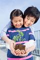 タイトル:植物の苗を持って立つ母と娘