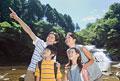 タイトル:渓流で上を見上げる家族4人